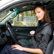 Woman fastens a seat belt in the car - Stock Photo