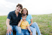 Happy beautiful young family posing outdoors — Stock Photo