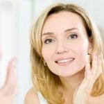 Beautiful woman applying cosmetic cream on face — Stock Photo