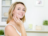 Beautiful smiling girl applying cream on face — Stock Photo
