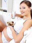 Mulher grávida comendo biscoitos doces com leite — Fotografia Stock