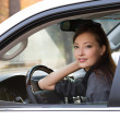 Young sexy woman in the new car — Stock Photo