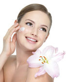 Happy teen with flower applying cream — Stock Photo