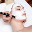 Cosmetician applying facial mask on female face — Stock Photo