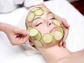 Woman receiving facial mask of cucumber — Stock Photo