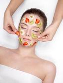 Woman getting fruit cosmetic facial mask — Stock Photo