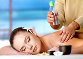 Woman getting massage with cosmetic oil in spa salon — Stock Photo