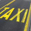 Yellow road sign on asphalt - Taxi. Belgrade. Serbia — Stock Photo