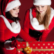 Two woman in Santa costume opening christmas gift. — Stock Photo