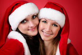 Two girl friends in christmass costumes on white. — Stock Photo