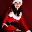 Beautiful brunette in Christmas dress opens gift. — Stock Photo