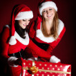 Foto Stock: Two woman in Santa costume opening christmas gift.