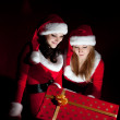 Two woman in Santa costume opening christmas gift. — Stock Photo #3932498