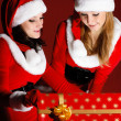 Two woman in Santa costume opening christmas gift — Stock Photo