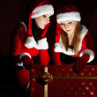Two woman in Santa costume opening christmas gift. — Stock Photo #3947469