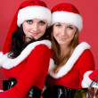 Two women in dressed as Santa, with shopping bags . — Stock Photo #3947492