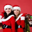Foto Stock: Two women in dressed as Santa, with shopping bags .