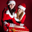 Stock Photo: Two womin Santcostume opening christmas gift.