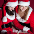 Two woman in Santa costume opening christmas gift. — Stock Photo #4118329