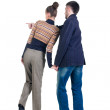 Young couple pointing at wall. Rear view. - Stock Photo