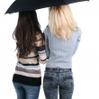 Two women under an umbrella. Rear view. — Stock Photo