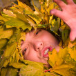 Woman covered by autumnal leaves — Stock Photo #4174514