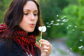 Girl blowing on dandelion — Stok fotoğraf