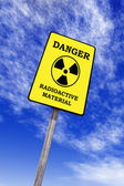 Radioactivity billboard on a blue sky with clouds — Foto de Stock