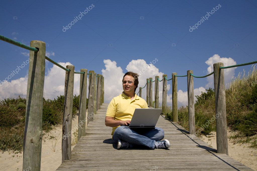 Young man working with computer at the beach — Stock Photo #4855601