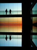 Silhouettes in a modern builing at sunset — Stock Photo
