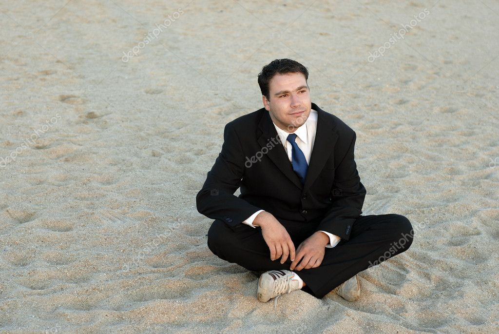 Young silly businessman at the beach with sunset light — Stock Photo #4892926