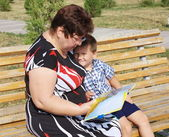 A grandmother reads a book to the grandchild — Стоковое фото