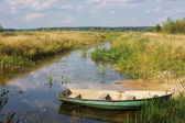 Old wooden boat ashore pond — Stock Photo