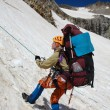 Mountaineer girl moving down on rope - Stock Photo
