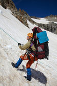 Mountaineer girl moving down on rope — Stock Photo