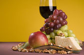 Red wine with grape, apple and cheese on a plate. — Stock Photo