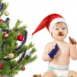 Stock Photo: Cute baby girl near the Christmas tree eats chocolate egg isolat