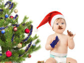 Cute baby girl near the Christmas tree eats chocolate egg isolat — Stock Photo