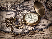 Vintage clock at antique map — Stock Photo