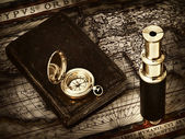 Vintage telescope and compass at antique map — Stock Photo