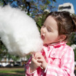 Girl eating candy-floss — Stock Photo