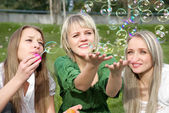 Girls inflating soap-bubbles — Stock Photo
