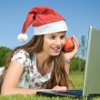 Girl with laptop lying on a grass — Stock Photo