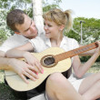Couple with a guitar in the park - Stock Photo