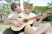 Couple with a guitar in the park — Stock Photo