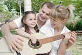 Family plaing guitar — Stock Photo