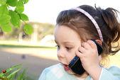 Meisje zit buiten met communicator — Foto de Stock