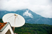 Satellite dish, roof and mountains — Stock Photo
