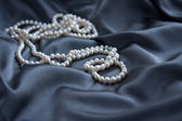 White pearls on blue satin — Stock Photo