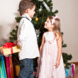 Foto Stock: Girl and boy near a fir-tree